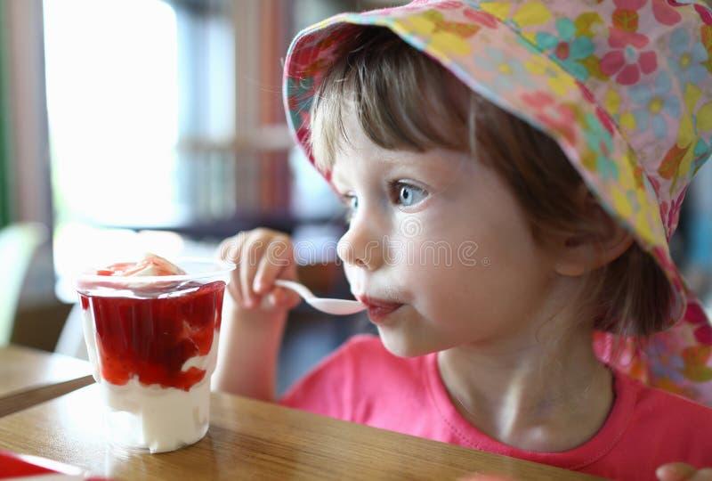 Le petit enfant satisfait lèche la cuillère avec de la glace photographie stock