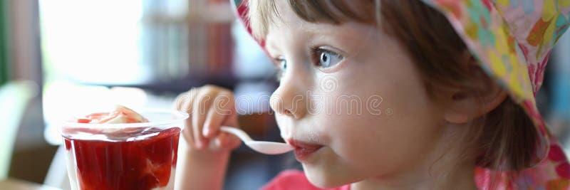 Le petit enfant satisfait lèche la cuillère avec de la glace image libre de droits