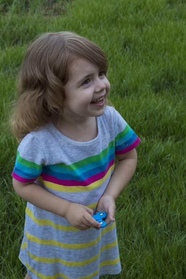 Le petit enfant sourit et joue avec le fileur sur le fond de l'herbe verte photo stock