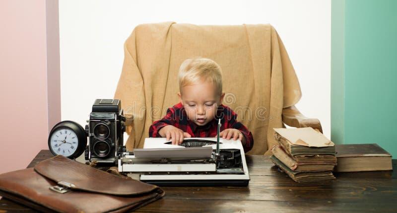 Le petit enfant tapent le papier à la machine sur la rétro machine à écrire au bureau Le garçon tapent des clés à la machine sur  photographie stock