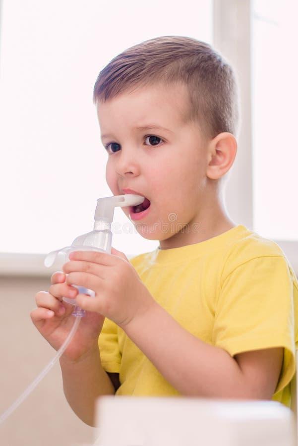 Le petit enfant traite l'inhalateur de bronchite ? la maison photo stock