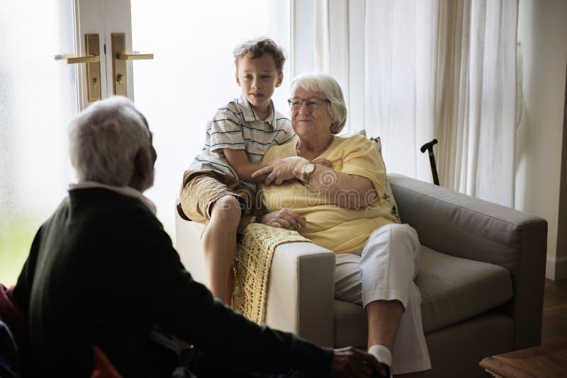 Le petit-fils est dans un salon avec des grands-parents photos libres de droits