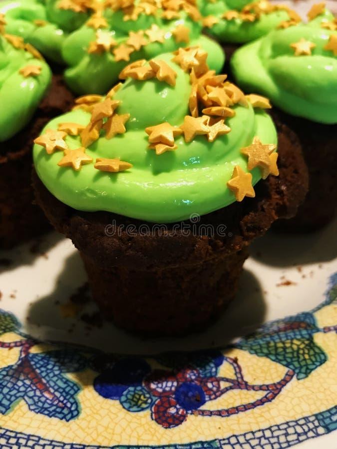 Le petit gâteau de chocolat avec se givrer vert et étoiles d'or arrose d'un plat mosaïque-modelé blanc photos stock