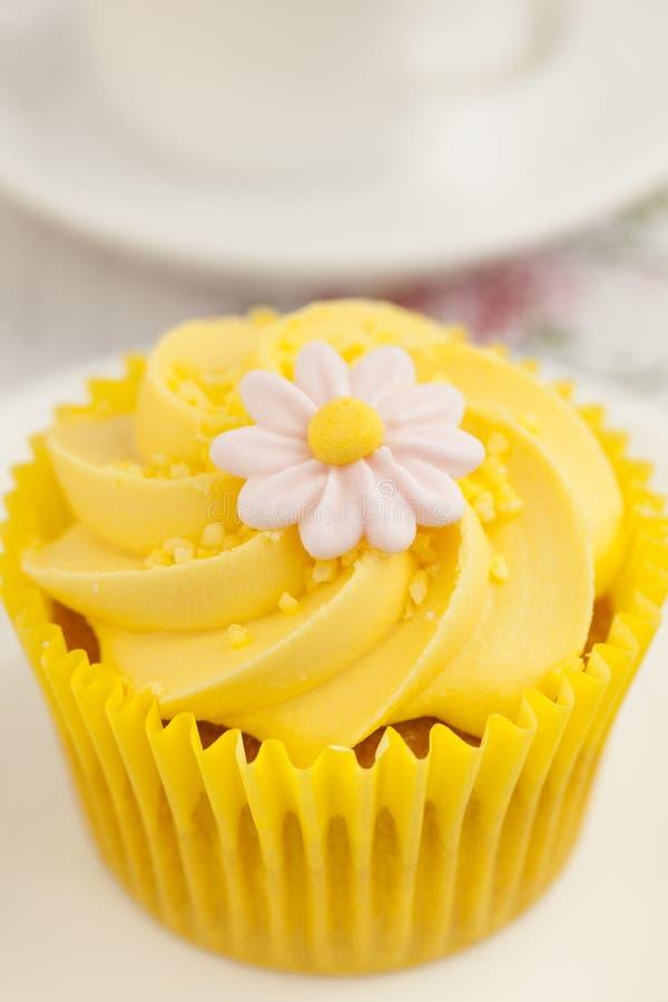 Le petit gâteau de citron avec le remous de crème de beurre et le fondant fleurissent la décoration photo libre de droits