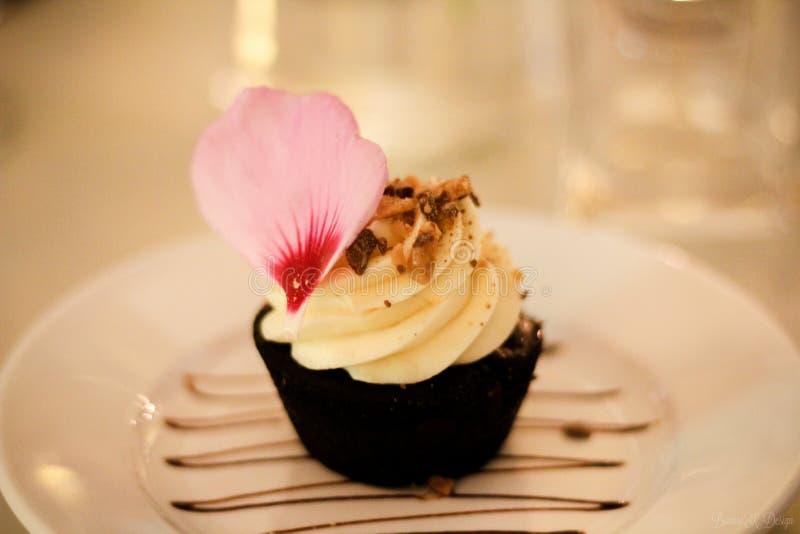 Le petit gâteau de vanille dans une tasse de chocolat a servi d'un plat en céramique blanc avec le pétale de fleur photographie stock libre de droits
