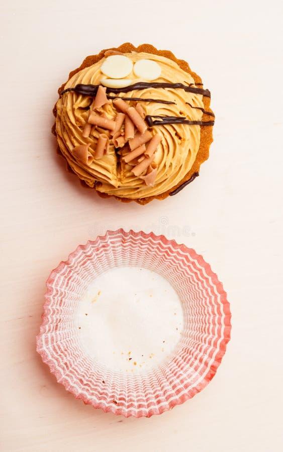 Le petit gâteau et le papier doux de nourriture forment sur la table image libre de droits