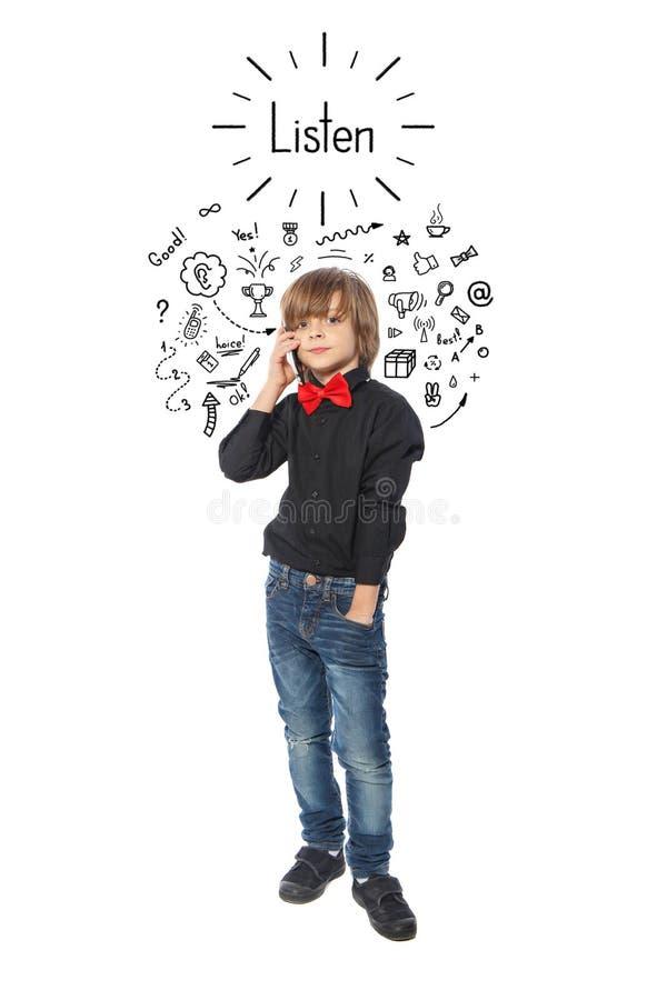 Le petit garçon écoute histoire au téléphone photographie stock