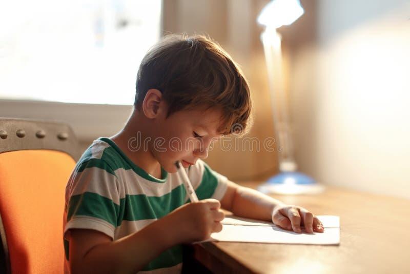 Le petit garçon écrivent au papier blanc images stock