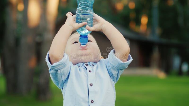 Le petit garçon a été eau potable de la bouteille pendant 1 année Position dans l'arrière-cour de votre maison photos stock