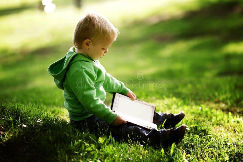 Le petit garçon affiche le livre photos libres de droits