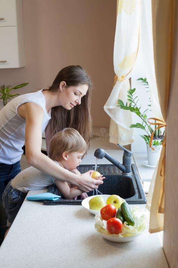 Le petit garçon aide la maman dans la cuisine photos libres de droits