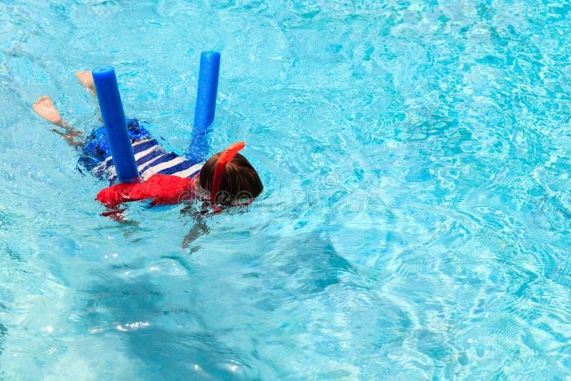Le petit garçon apprend seule la natation avec la nouille de piscine image stock