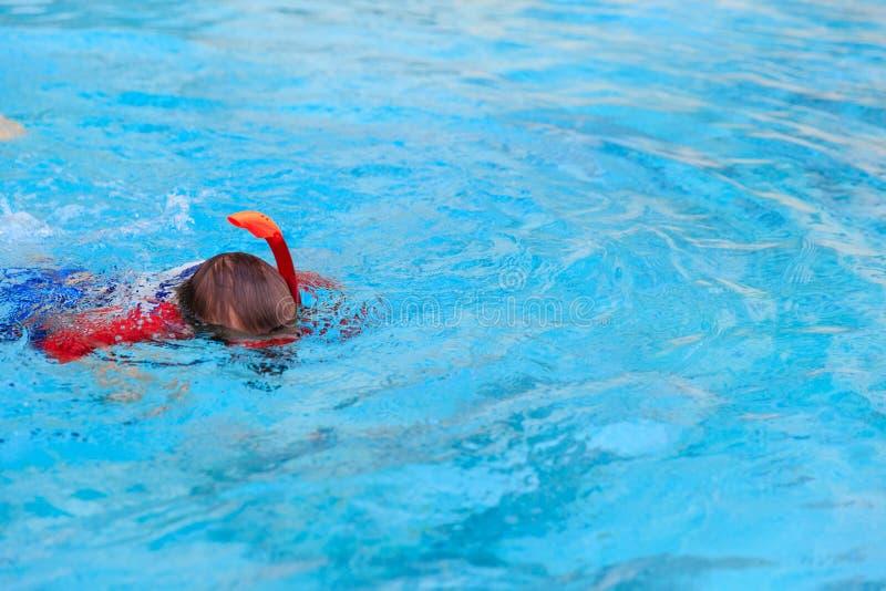 Le petit garçon apprend seule la natation dans la piscine photos stock