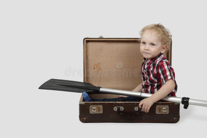 Le petit garçon avec l'aviron s'assied dans la valise de vintage photo stock