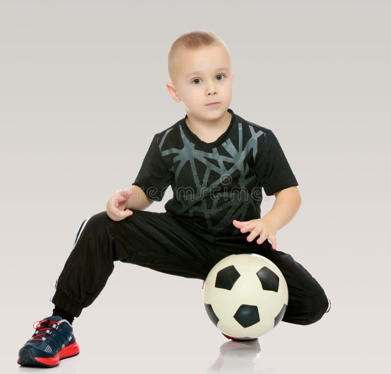 Le petit garçon avec la boule dans des ses mains photographie stock libre de droits