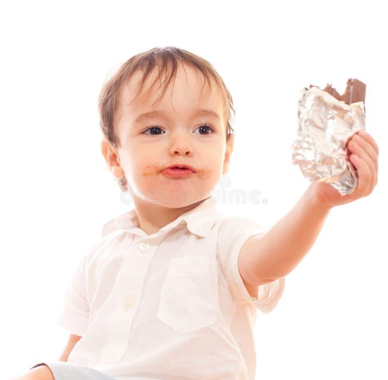 Le petit garçon avec les languettes modifiées offre le bar du chocolat image stock