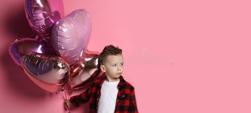 Le petit garçon avide ne veut pas donner des ballons quiconque de coeur image libre de droits