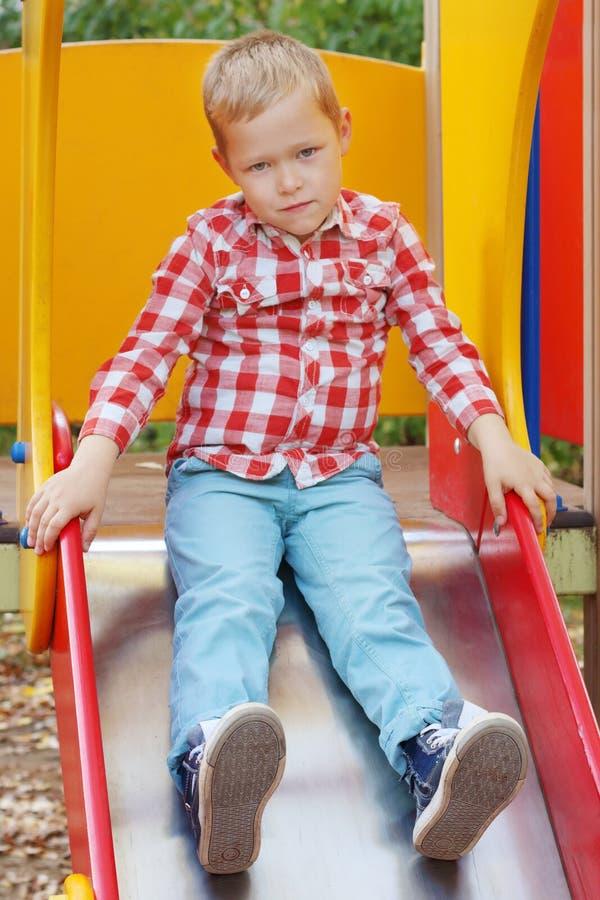 Le petit garçon beau dans la chemise s'assied sur la glissière photos stock