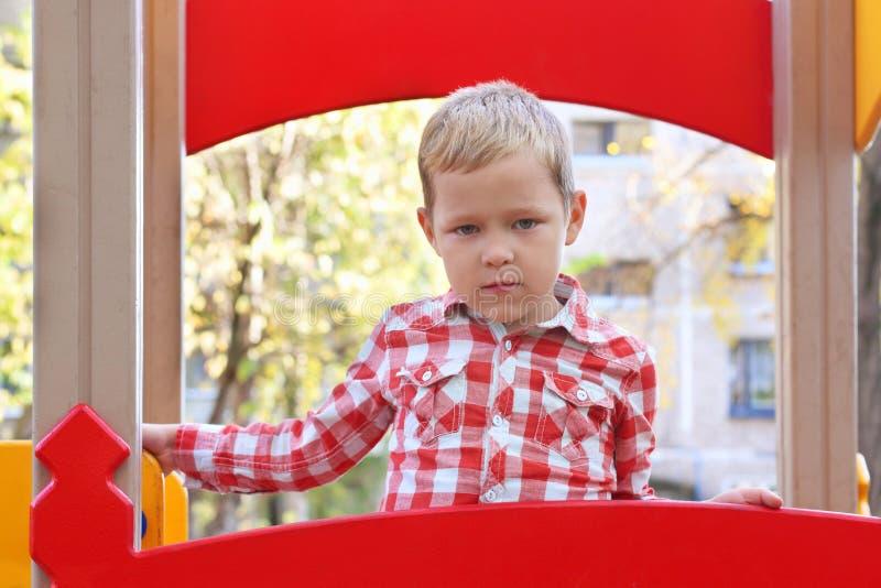 Le petit garçon beau dans la chemise se tient sur le terrain de jeu photo libre de droits