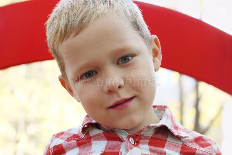 Le petit garçon beau dans la chemise sourit sur le terrain de jeu images stock