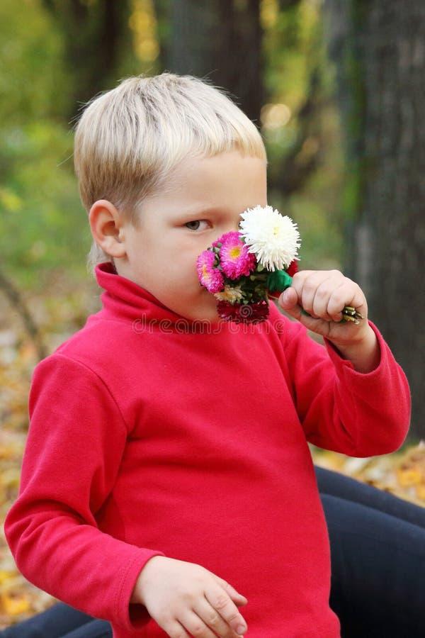 Le petit garçon blond en rouge renifle des fleurs photographie stock