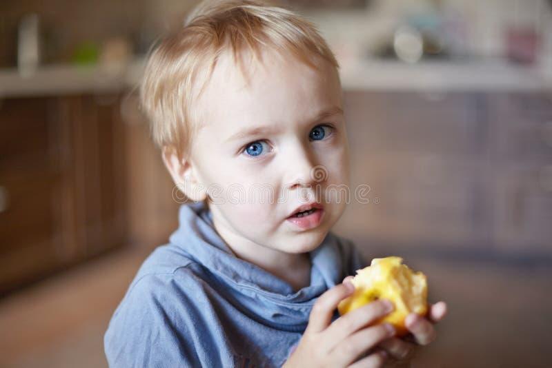 Le petit garçon caucasien mignon avec des yeux bleus et des cheveux blonds mange la pomme jaune, les tenant sur les mains images libres de droits