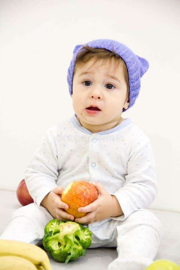 Le petit garçon caucasien mignon 11 mois repose et mange la pomme rouge sur le fond blanc photos libres de droits