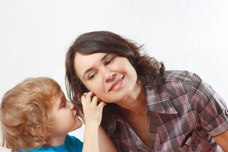 Le petit garçon chuchote quelque chose à sa mère image libre de droits