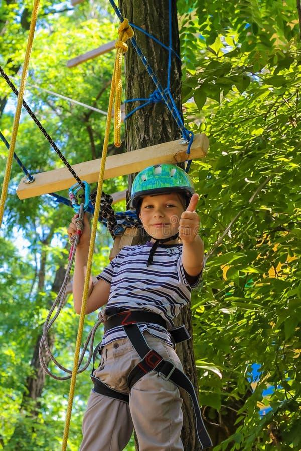 Le petit garçon courageux a un amusement au parc d'aventure et des pouces de donner images stock