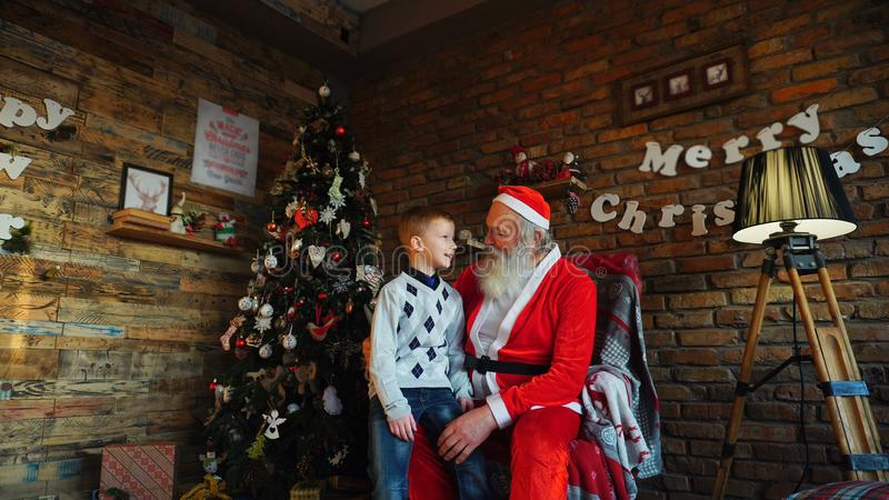 Le petit garçon court à Santa et met le désir sur l'oreille de Santa s r photo libre de droits