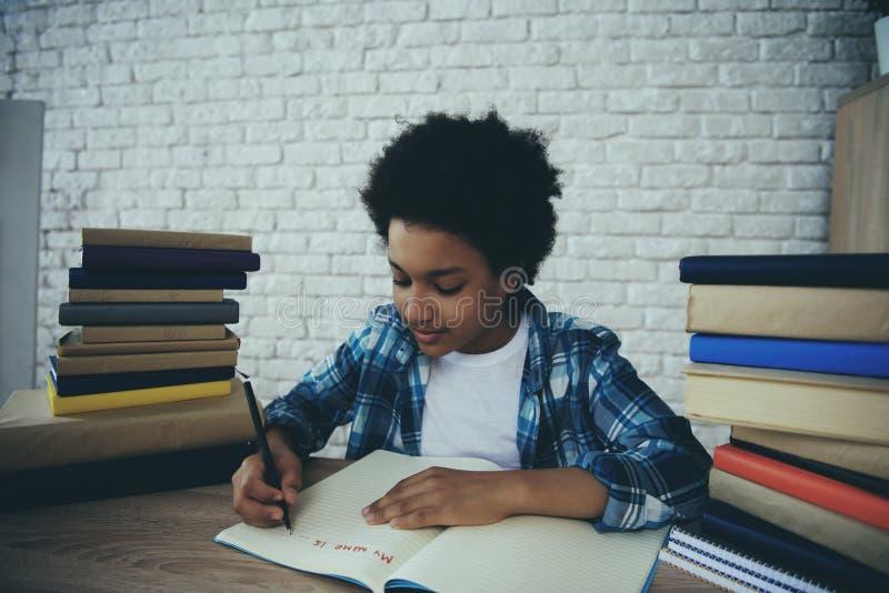 Le petit garçon d'afro-américain fait le travail à la maison photo libre de droits