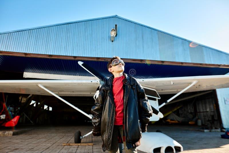Le petit garçon dans la grande veste pilote regarde dans le ciel, rêvant de voler loin photos libres de droits