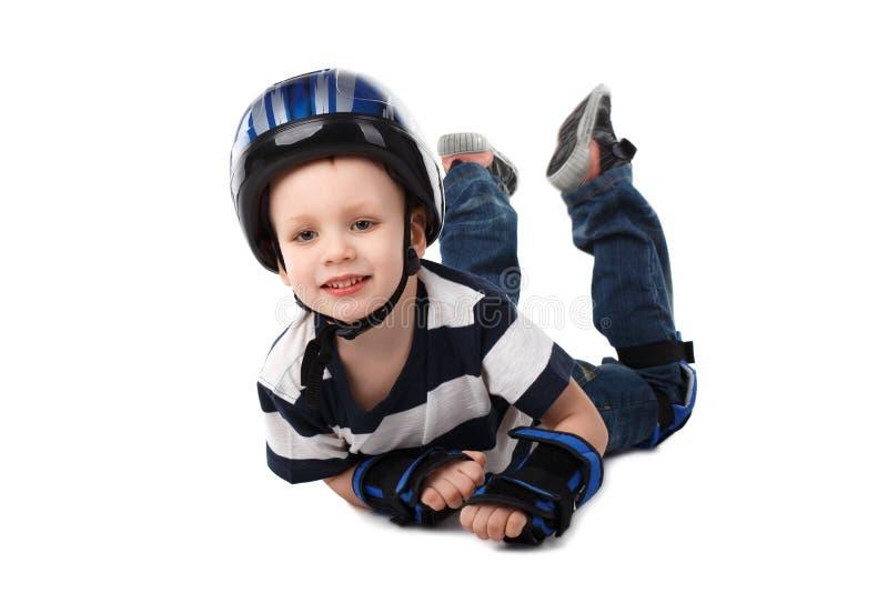 Le petit garçon dans la vitesse protectrice a tombé sa bicyclette ou scooter ou photo stock