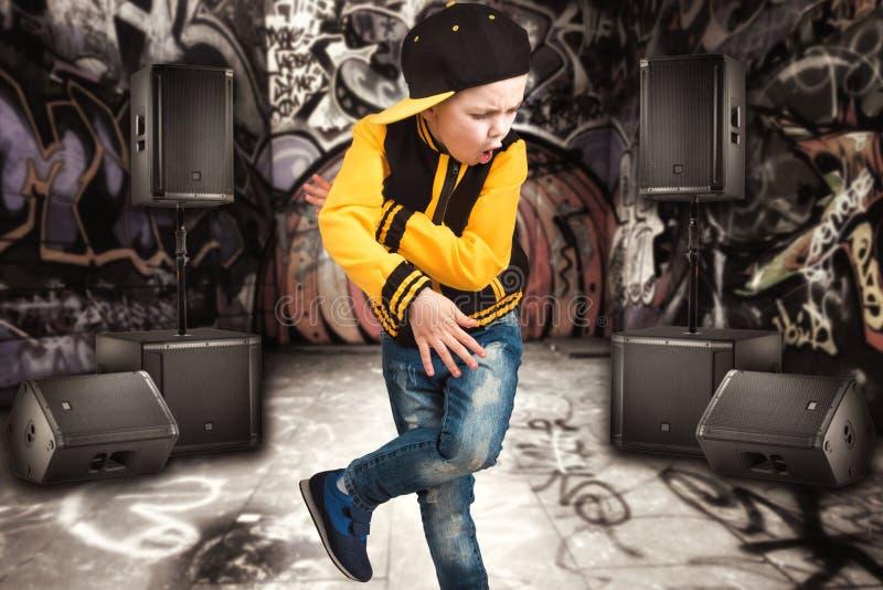 Le petit garçon dans le style du hip-hop Mode du ` s d'enfants Chapeau et veste Le jeune frappeur Graffiti sur les murs Refroidis images stock