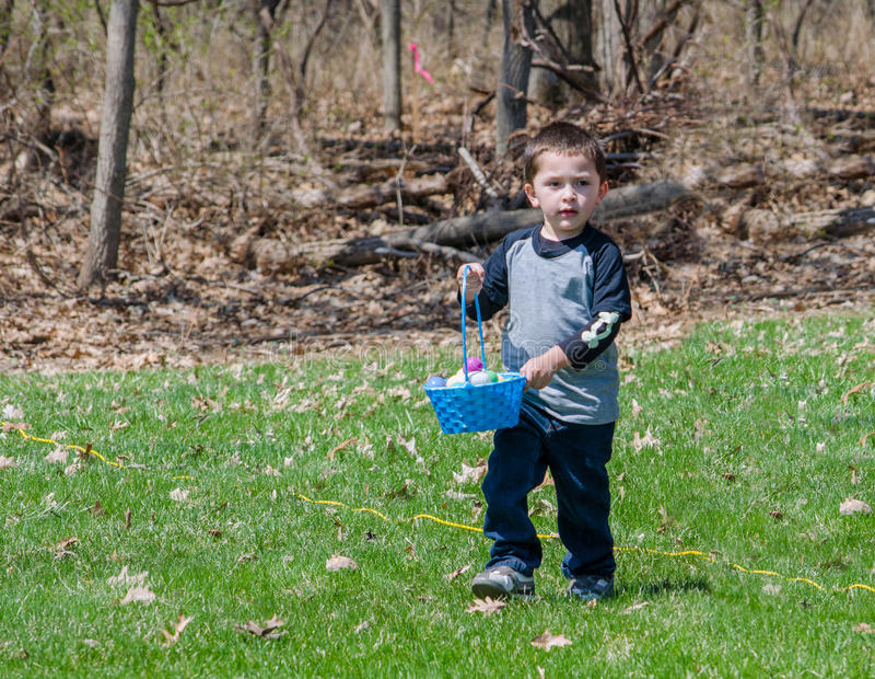 Le petit garçon dans un oeuf de pâques chassent dehors photo stock