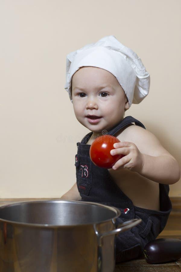 Le petit garçon dans une toque en tant que cuisinier de chef photographie stock libre de droits