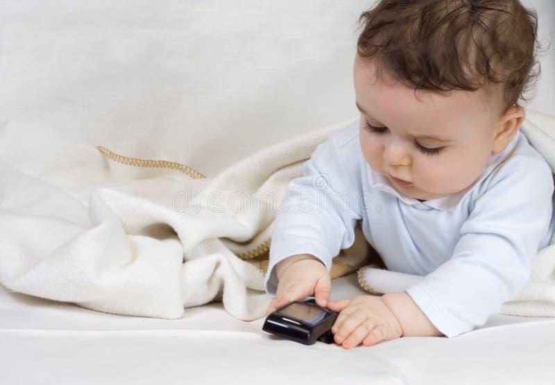 Le petit garçon de 7 mois joue avec un t cellulaire photos libres de droits