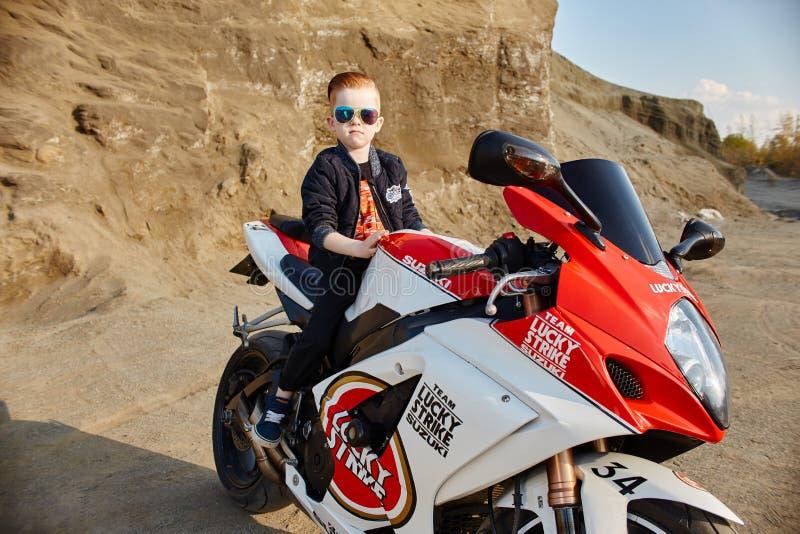 Le petit garçon de jeunes s'asseyant sur une moto de emballage, un beau petit motard sur des sports font du vélo en nature Fils d image libre de droits