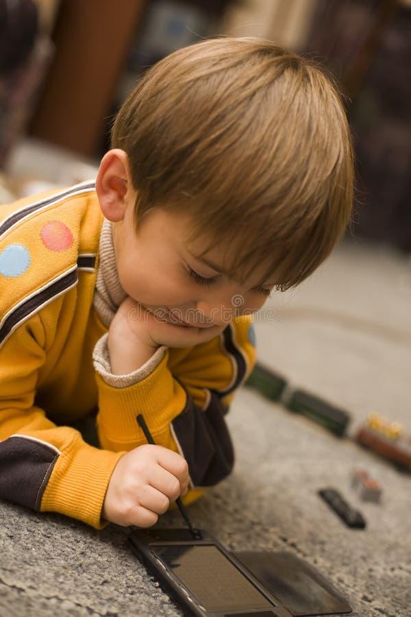 Le petit garçon de sourire joue le jeu de logique sur le PPC photos libres de droits