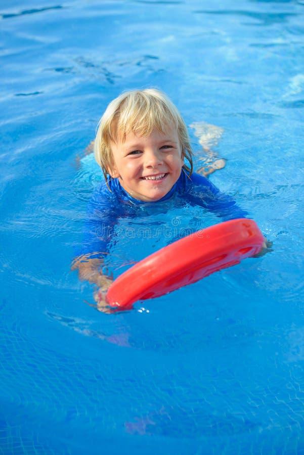 Le petit garçon de sourire a l'amusement avec le conseil de flottement dans la piscine image stock