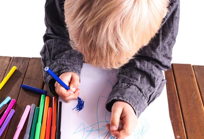 Le petit garçon dessine un dessin photo stock