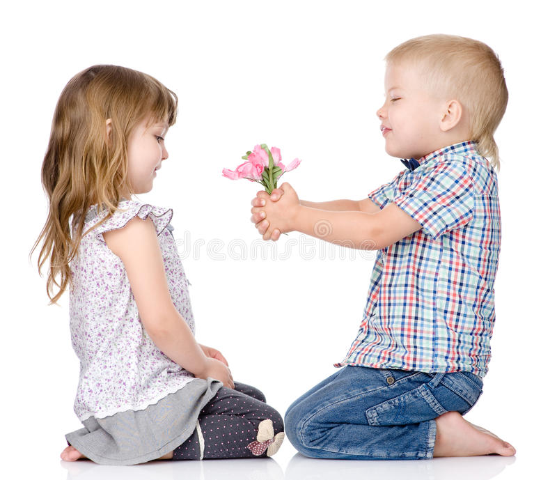 Le petit garçon donne à la fille une fleur D'isolement sur le blanc images stock