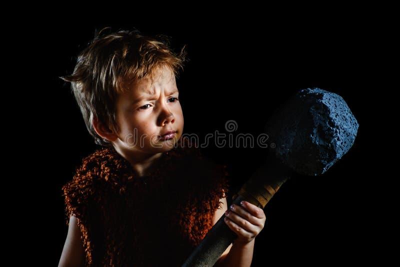Le petit garçon drôle est un neanderthal ou un hôte-Magnon Un homme des cavernes antique avec une hache énorme est isolé sur un n images stock