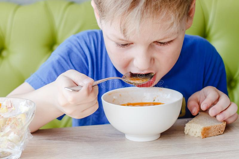 Le petit garçon est appétissant mangeant d'une soupe délicieuse avec une grande cuillère images libres de droits