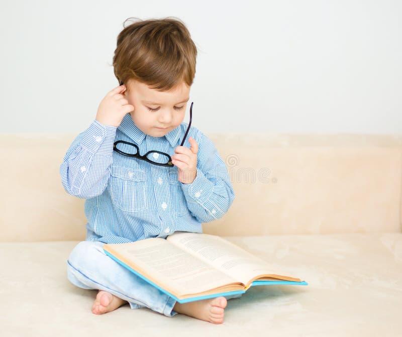 Le petit garçon est livre de lecture image stock