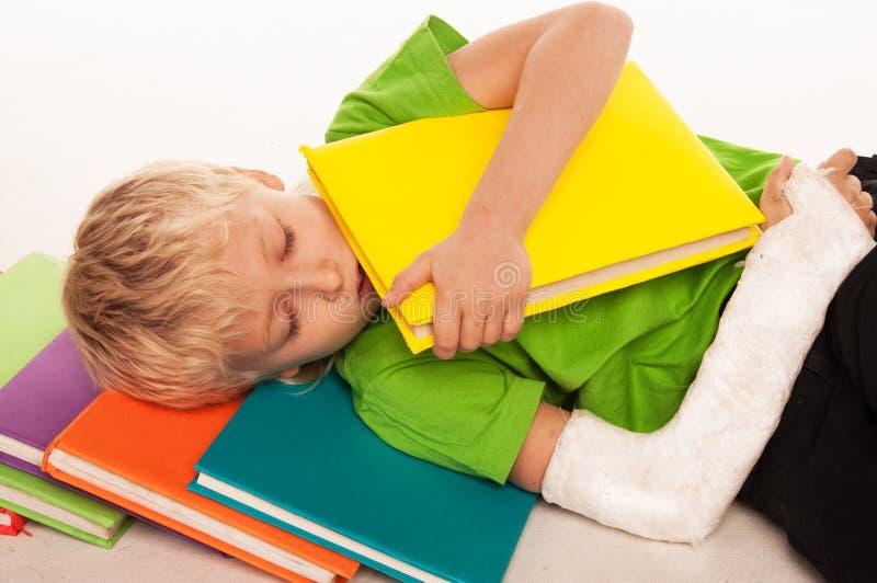 Le petit garçon est tombé endormi sur des livres photo libre de droits