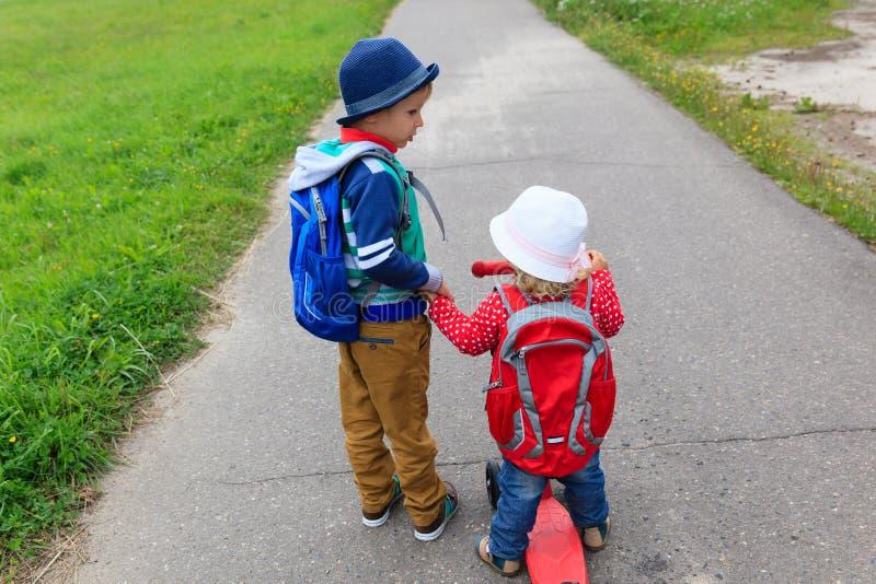 Le petit garçon et la fille avec des sacs à dos sur la rue, enfants vont à l'école images stock