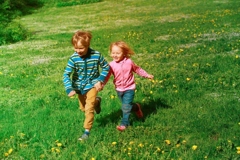 Le petit garçon et la fille heureux courent au printemps la nature image libre de droits