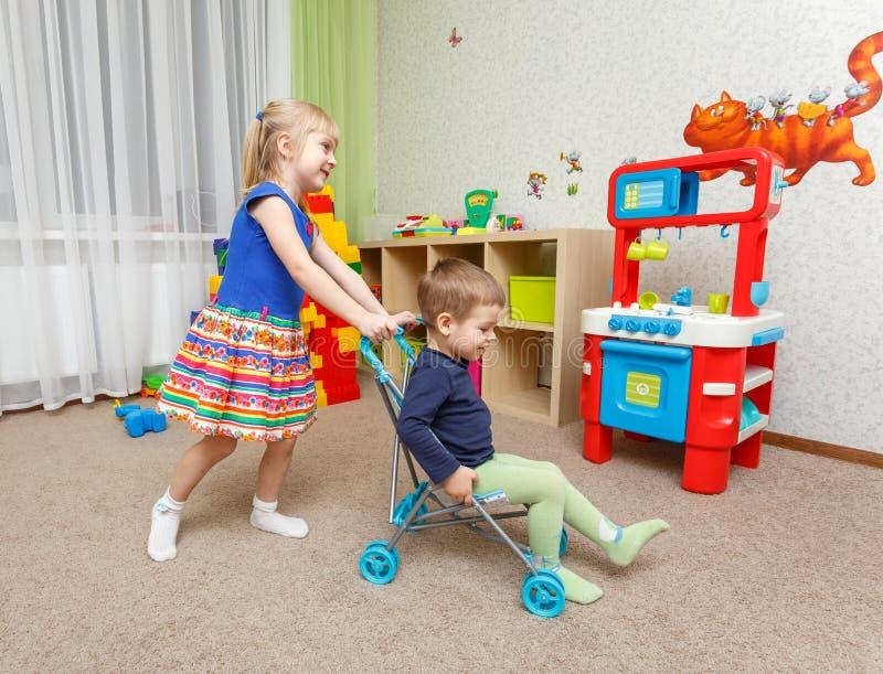 Le petit garçon et la fille jouent avec la poussette de jouet à la maison photo stock