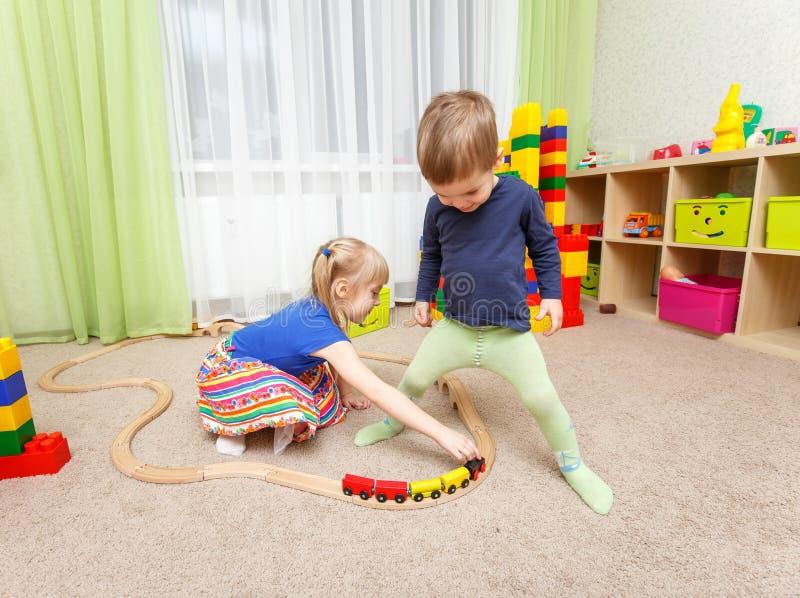 Le petit garçon et la fille jouent avec le chemin de fer de jouet dans le jardin d'enfants images libres de droits